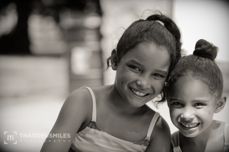 Two young girls smile for the camera. Day 338 of Thaddeus Miles's 365 Faces Photography Project. Posted on The Black Lion Journal.