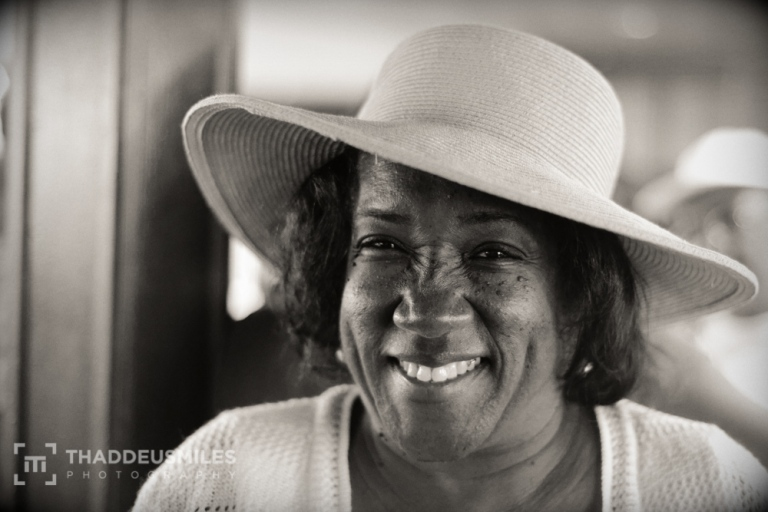 A woman wearing a hat smiles for the camera. Day 341 of Thaddeus Miles's 365 Faces Photography Project. Posted on The Black Lion Journal.